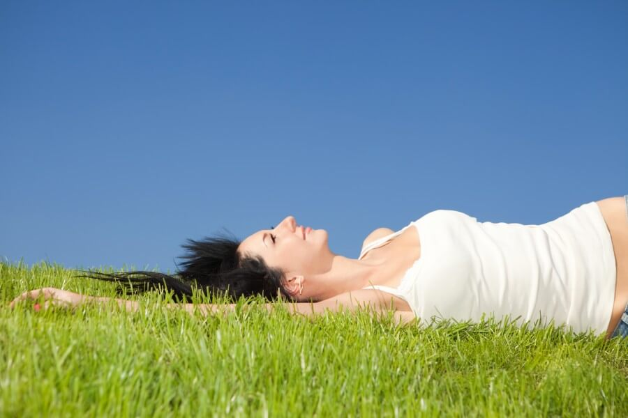 happy woman resting on the green grass